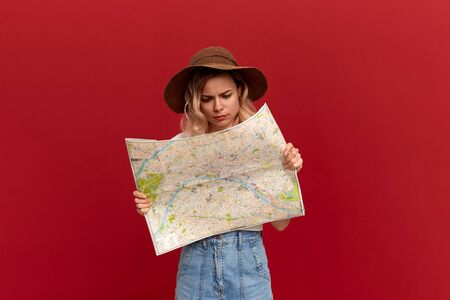 Pretty blond girl with curly hair in a white t-shirt and a sundown hat looks at the camera holding map trying to find itinerary while traveling.. Concept of travel