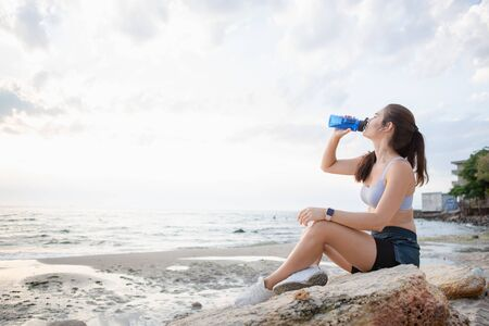 Portrait of a young brunette woman with wireless earbuds and smart watches resting after morning exercising at the sea shore at sunrise drinking water