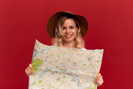 Happy blond girl with curly hair in a white t-shirt and a sundown hat looks at the map looking for itinerary while traveling. Concept of travel