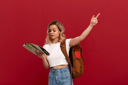 Blond tourist with curly hair in a white t-shirt pointing with a hand at the right during sightseeing tour holding map and orange backpack. Concept of travel