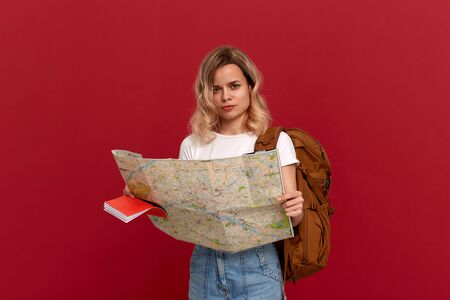Thoughtful blond girl with curly hair in a white t-shirt looks at the map trying to find itinerary holding orange backpack. Concept of travel