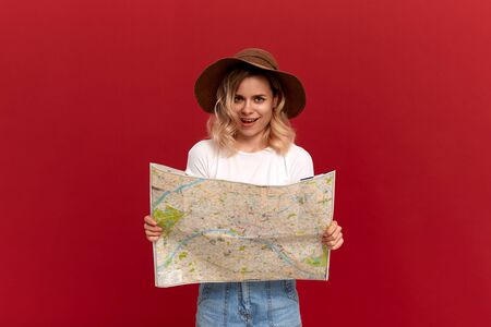 Happy blond girl with curly hair in a white t-shirt and a sundown hat holds map looking for itinerary while traveling. Concept of travel