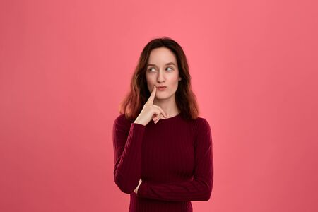 Beautiful young lady standing isolated over pink background with finger raised close to mouth expressing gesture of thoughtfulness. Concept of idea and thinking Imagens
