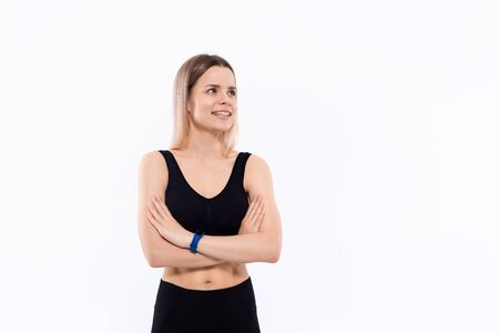 Young sporty blond woman in a black sportswear with smart watches for pulse measuring keeping hands crossed standing over white background looking to the left. Place for advertisement.