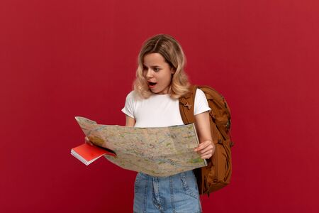 Shocked blond girl with curly hair in a white t-shirt looks at the map trying to find itinerary holding brown backpack. Concept of travel