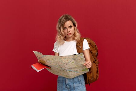 Shocked blond girl with curly hair in a white t-shirt looks at the map trying to find itinerary holding orange backpack. Concept of travel