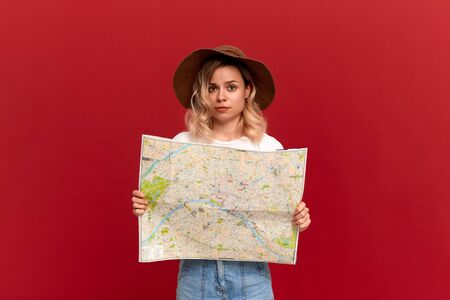 Shocked blond girl with curly hair in a white t-shirt and a sundown hat looks at the camera holding map trying to find itinerary while traveling. Concept of travel
