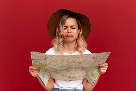 Shocked blond girl with curly hair in a white t-shirt and a sundown hat looks at the map trying to find itinerary while traveling. Concept of travel