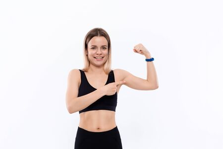 Happy young sporty blond woman in a black sportswear  showing bicep standing over white background.