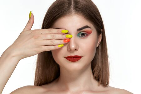 Closeup portrait of beautiful young woman with bright color make-up holding one hand with bright  manicure close to face. Isolated over white background.