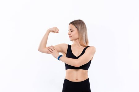 Young sporty blond woman in a black sportswear  showing bicep standing over white background. Stock Photo