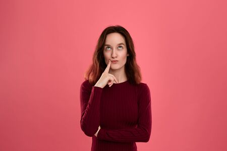 Beautiful young lady standing isolated over pink background with finger raised close to mouth reflecting about some idea. Concept of idea and thinking Imagens