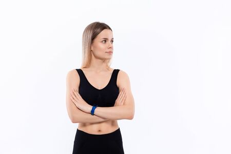 Young sporty blond woman in a black sportswear with smart watches for pulse measuring keeping hands crossed standing over white background looking to the right. Place for advertisement.