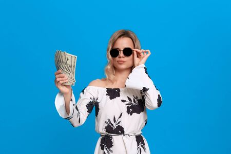 Portrait of a girl with curly blond hair in a white dress and dark sunglasses standing on a blue background looking surprisingly at the bundle of dollars. Фото со стока