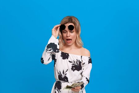 Portrait of a girl with curly blond hair in a white dress and dark sunglasses standing on a blue background looking surprisingly at the pack of dollars.