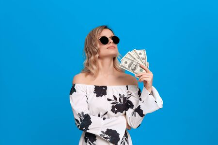 Portrait of a girl with curly blond hair in a white dress and dark sunglasses standing on a blue background. Happy model fans herself with a bundle of dollars with dreamy look.