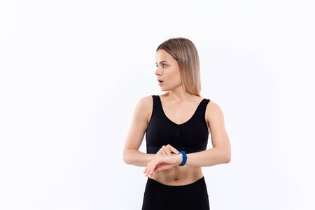 Young sporty blond woman in a black sportswear surprised havig checked pulse with smart watches after workout standing over white background. Concept of sport activity