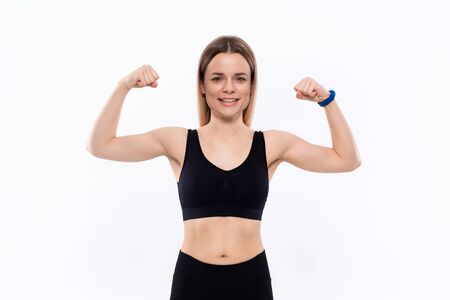 Young sporty blond woman in a black sportswear smiling showing biceps standing over white background.