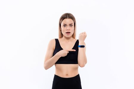 Young sporty blond woman in a black sportswear surprised checking pulse with smart watches after workout standing over white background. Concept of controlled sport activity Stock Photo