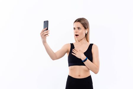 Young sporty blond woman in a black sportswear making selfie with smartphone showing bicep after workout standing over white background. Concept of sport activity