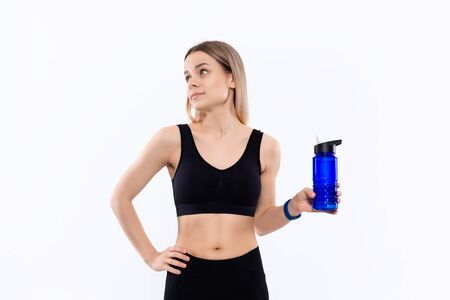Young sporty blond woman in a black sportswear with smart watches holds bottle with water after workout standing over white background. Concept of controlled sport activity