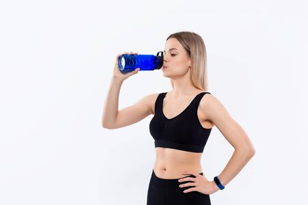 Young sporty blond woman in a black sportswear with smart watches drinks water after workout standing over white background. Concept of controlled sport activity