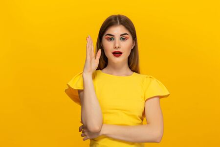 Close-up portrait of a beautiful young girl lifting a hand to ask a question isolated over yellow background. Gesture of question. Banco de Imagens