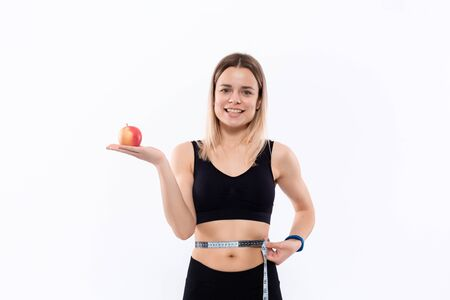 Young blond woman in a black sportswear with smart watches is happy checking waist after workout with the tape measure holding red apple standing over white background. Concept of weight loss.