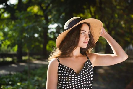 Close-up porttrait of a beautiful young brunette woman dressed in a black dress and a hat with wide flaps takes a walk in a park during warm summer day enjoying sunlight. Relaxing during promenade.