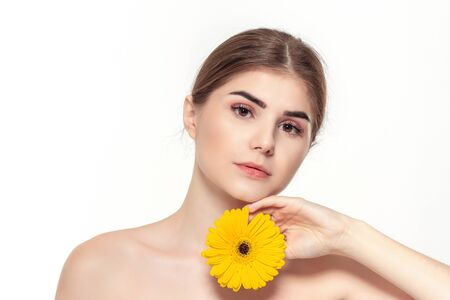 Close-up portrait of a beautiful young girl with yellow flower isolated over white background. Concept of beauty and health care.