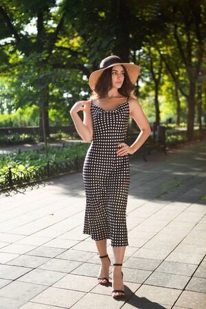 Beautiful young brunette woman dressed in a black dress and a hat with wide flaps takes a walk in a park during warm summer day enjoying sunlight. Relaxing during promenade.