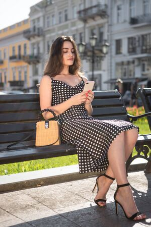 Beautiful girl in a black dress sits on a bench holding smartphone resting after sightseeing tour in old European town. Concept of communication while travelig