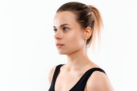 Portrait of a young sporty blond woman in a black sportswear exercising isolated over white background. Stock Photo