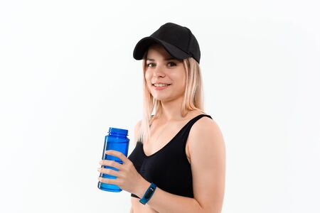 Young sporty blond woman in a black sportswear with smart watches holds bottle with water after workout standing over white background. Concept of controlled sport activity Stock Photo - 129386323