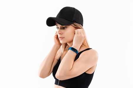 Young sporty blond woman in a black sportswear with smart watches listens to music during workout standing over white background. Listening to music during sport training. Stock Photo