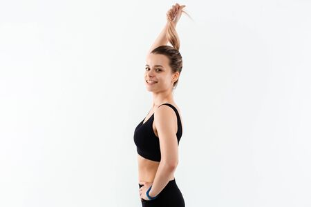 Young sporty blond woman in a black sportswear exercising isolated over white background.