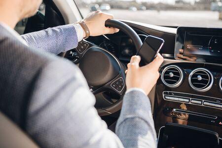 Junger Geschäftsmann, der Handy beim Autofahren betrachtet.