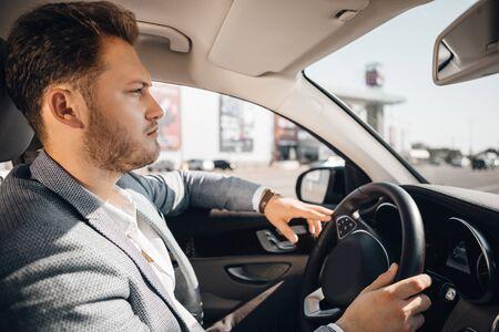 Un uomo d'affari di successo in giacca e cravatta guida la sua auto di lusso.