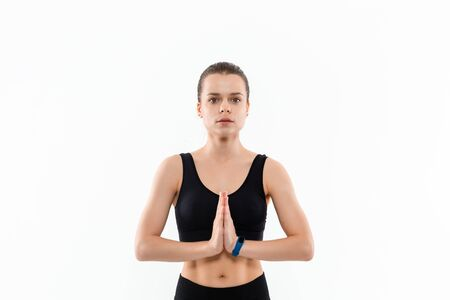 Young sporty blond woman in a black sportswear relaxing after exercising isolated over white background.