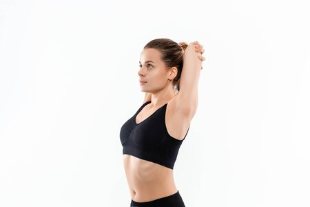 Young sporty blond woman in a black sportswear stretching before exercising isolated over white background.
