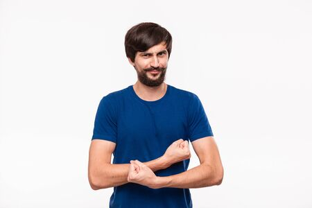 Funny good looking brunet bearded man with mustaches in a blue shirt showing biceps standing isolated over white background. Desire to be strong.