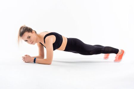 Young sporty blond woman in a black sportswear holding plank position exercising isolated over white background. Stock Photo