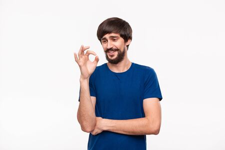Handsome brunet bearded man with mustaches in a blue shirt hesitatingly showing gesture of OK sign standing isolated over white background. OK gesture.