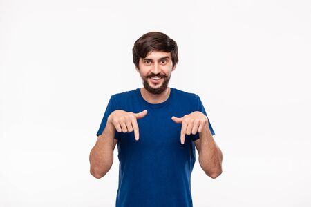 Good looking brunet man in a blue shirt with beard and mustaches pointing with his fingers down standing isolated over white background. Place of product and advertisment. Imagens