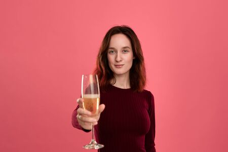 Excited pretty brunette girl holding wineglass of sparkling champagne standing isolated on a dark pink background and smiling at the camera. Celebrating special event.