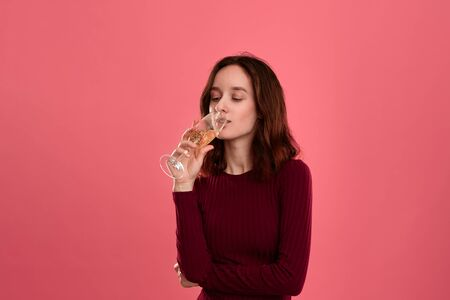 Excited pretty brunette girl drinking sparkling champagne from a wineglass standing isolated on a dark pink background. Celebrating special event. Stock Photo