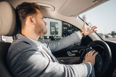 Angry driver in a traffic jam loosing his tamper and gesturing to let his car go. Being late Stock Photo