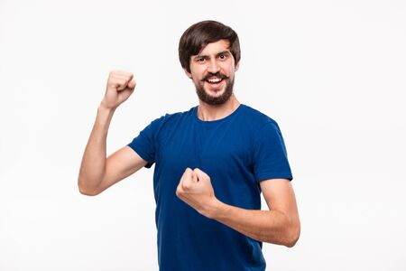 Young brunet bearded man with mustaches in a blue shirt posing expressing gesture of victory with his arms standing isolated over white background. Concept of success.