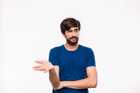 Handsome bearded brunet man in a blue shirt holding arms folded over his chest and throwing one hand in the air with sceptical emotion standing isolated over white background. Emotion of doubt.