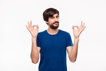 Handsome brunet bearded man with mustaches in a blue shirt showing gesture of OK sign with two hands standing isolated over white background. OK gesture.